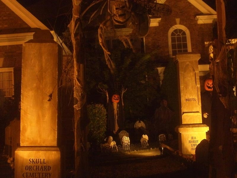 Night View of Halloween Graveyard Entrance Bat Skeleton Skull Orchard Cemetery and Scarecrow
