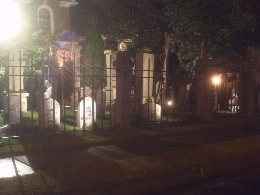 Night View of Halloween Graveyard Entrance Banner Bat Skeleton Skull Orchard Cemetery and Scarecrow